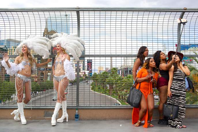 UNLV students, Destiny Penna, left, and Chaslina Cress work as showgirls for tips while friends from Bronx, New York - who came to Las Vegas for the fight, pose for a group selfie outside the MGM Grand in the midst of pre-fight excitement on the Las Vegas Strip on Saturday, May 2, 2015.